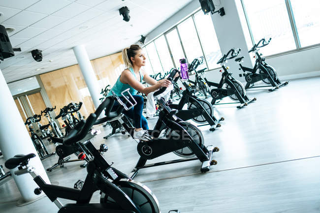Woman with towel and water on exercise machine — Stock Photo