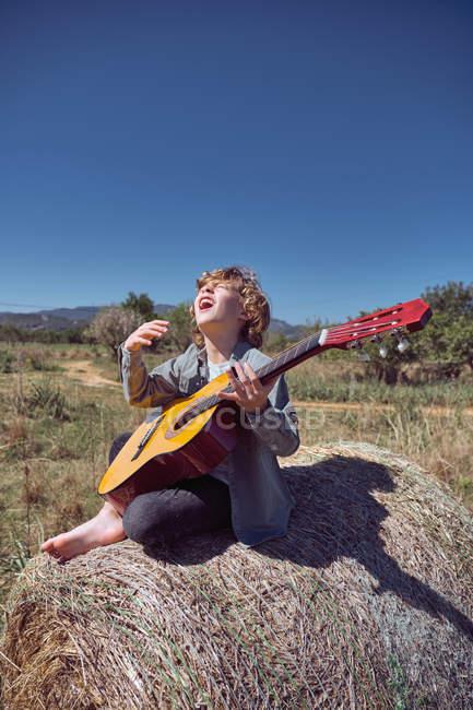 Netter Junge, der Akustikgitarre spielt und singt, während er an einem sonnigen Tag im Grünen in einer riesigen Rolle trockenem Heu sitzt — Stockfoto