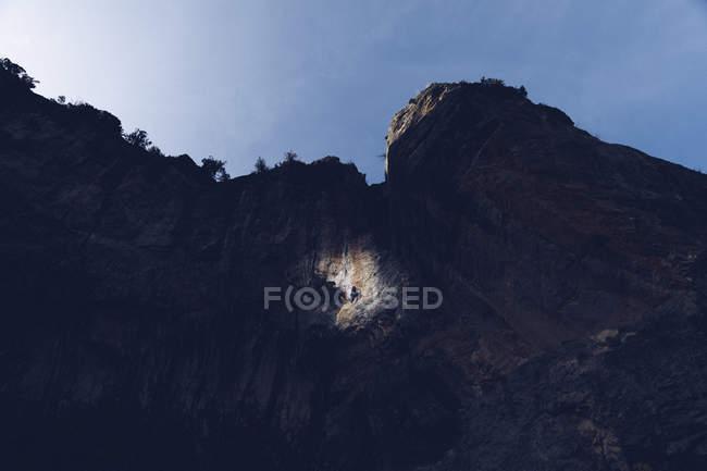 Dal basso di enorme scogliera rocciosa scura con persona che si arrampica in un punto di luce sotto il cielo blu — Foto stock