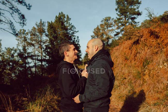 Glückliches homosexuelles Paar umarmt sich an sonnigem Tag auf Waldweg — Stockfoto
