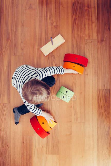 Loira bonito menino jogando com waldorf arco-íris quebra-cabeça — Fotografia de Stock