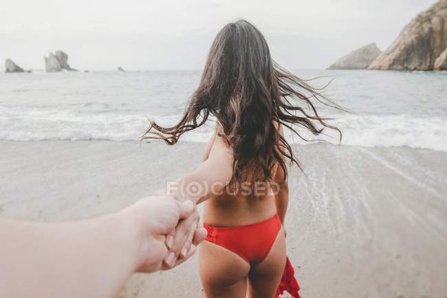 Retro vista di nudo bruna signora in lingerie tenendo mano raccolto di maschio sulla costa vicino al mare — Foto stock