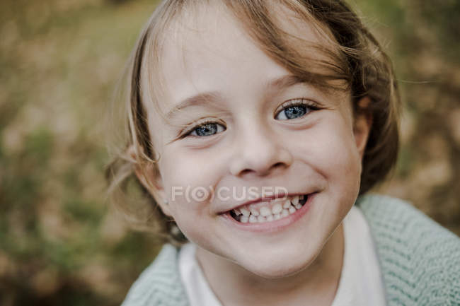 Portrait of positive little girl looking at camera on blurred background in nature — Stock Photo