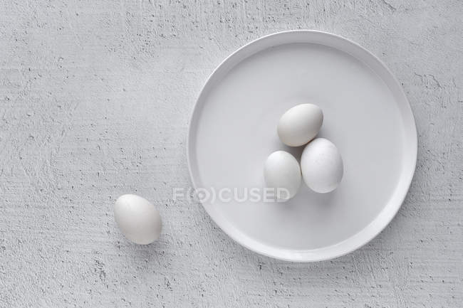 White eggs on plate on wooden table — стоковое фото