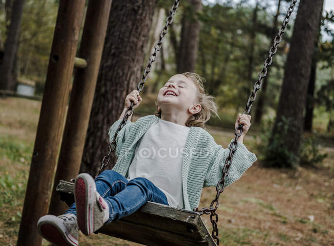 Positive happy child sitting on swings between trees in forest — Stock Photo