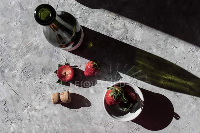 Свежая клубника в миске и на серой поверхности с бутылкой вина — стоковое фото