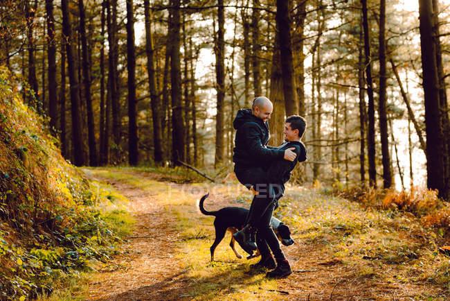 Гомосексуальная пара обнимается с собакой на пути в лес в солнечный день — стоковое фото