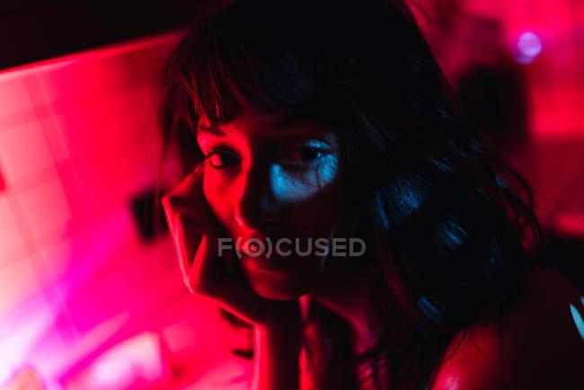 Primer plano de sensual joven morena mujer mirando a la cámara y sentado en la cocina entre el enrojecimiento - foto de stock