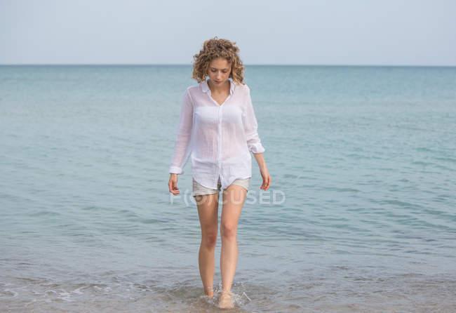 Giovane donna affascinante in camicia bianca che cammina in acqua di mare — Foto stock