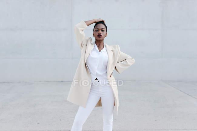 Moda donna etnica dai capelli corti in abito bianco in posa contro muro grigio — Foto stock