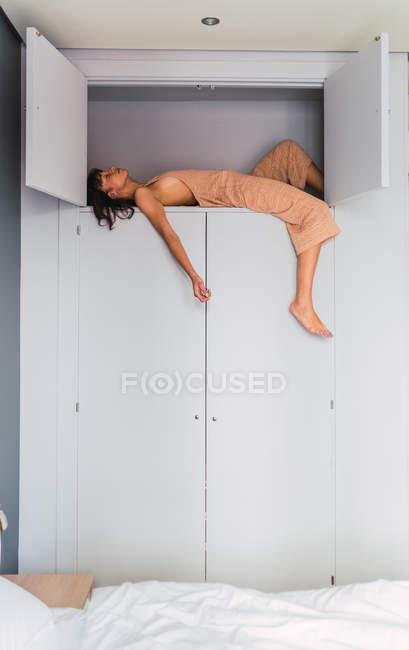 Junge sinnliche Frau schläft auf hohem Regal des Kleiderschranks neben Bett im Schlafzimmer — Stockfoto