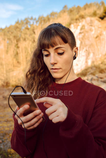Young hipster woman with piercing and earphones listening music with mobile phone and walking on countryside road — Stock Photo
