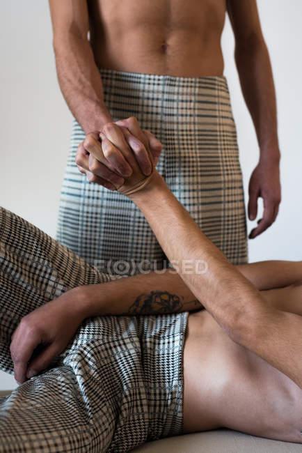Imagen recortada de elegantes modelos de pareja gay sin escrúpulos que ponen manos a la obra y se asientan en un elegante banco moderno. - foto de stock