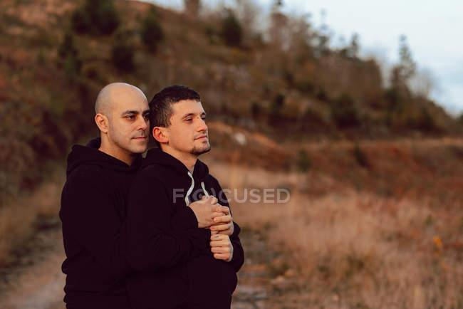 Мечтательная гомосексуальная пара, обнимающаяся на маршруте в природе — стоковое фото