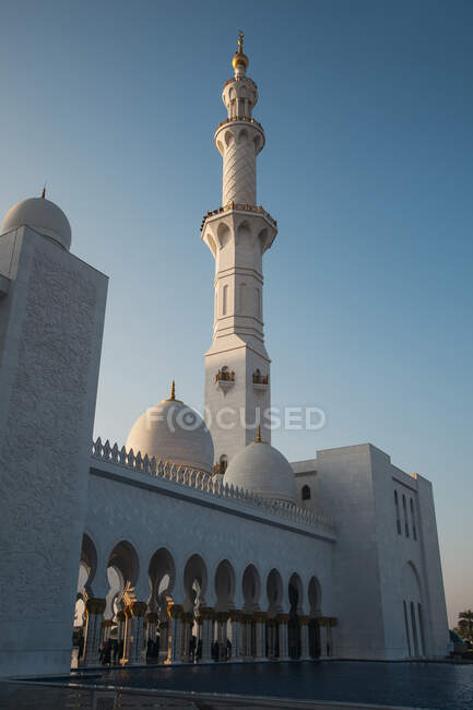 Amazing huge mosque with high tower near pool and blue sky in Abu Dhabi, United Arab Emirates — Stockfoto