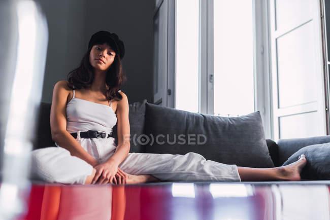 Приваблива молода стильна жінка в шапці дивиться на камеру відпочиваючи на дивані біля балкона будинку — стокове фото