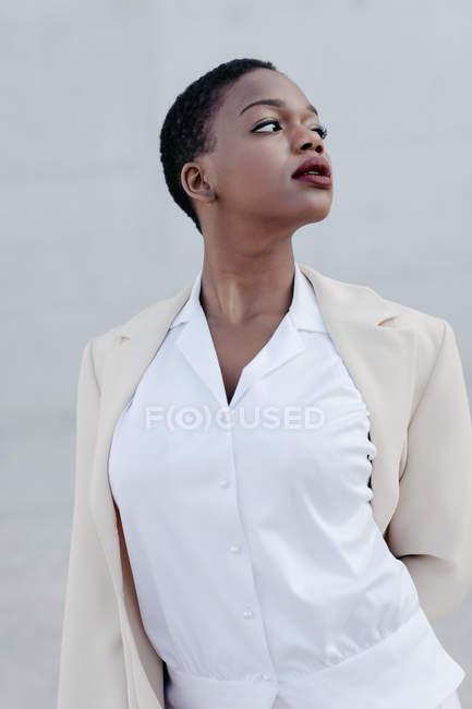 Sinnliche Mode kurzhaariges ethnisches Model im weißen Outfit posiert gegen graue Wand — Stockfoto