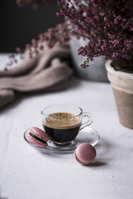 Cup of fresh brewed espresso in glass cup served with pink macaroons on table — Stock Photo