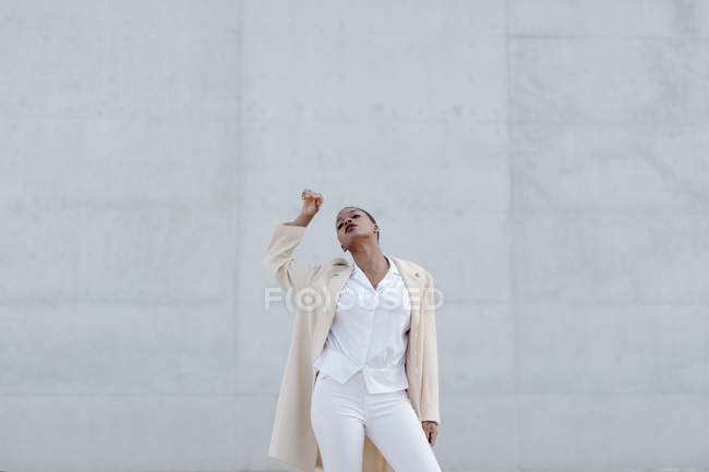 Sensual fashion short haired model in white outfit posing against grey wall — Stock Photo
