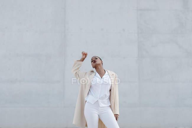 Moda sensuale modello a pelo corto in abito bianco in posa contro muro grigio — Foto stock