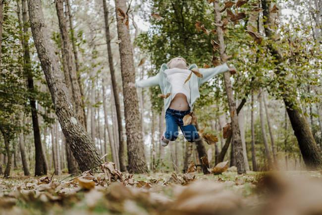 Bambino positivo che salta sul fogliame secco nella foresta — Foto stock