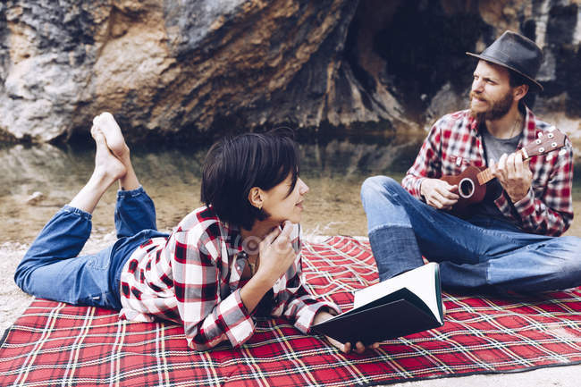 Adult man and woman on checkered plaid with book and small ukulele having picnic on lake shore — Stock Photo