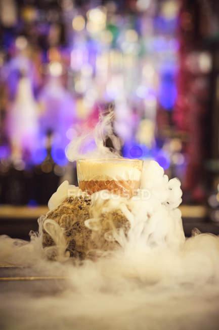 Чашка вкусного коктейля, излучающего густой пар во время размещения на прилавке на размытом фоне бара — стоковое фото