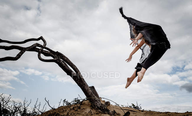 From below young ballerina in black wear with upped hands in air near dry branches and blue sky in clouds — Stock Photo