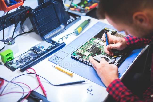 Focused man repairing laptop at workplace — Stock Photo