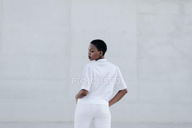 Élégante femme à poil court à la mode en tenue blanche posant contre la construction grise — Photo de stock