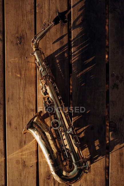 Golden saxophone on old wood shining in sunlight — Stock Photo