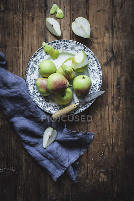 Juicy fresh pears on plate on wooden table with knife and napkin — Stock Photo