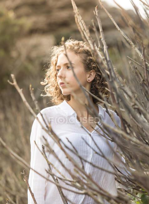 Молода жінка замислений стоїть біля сухих гілок чагарників на розмите тло — стокове фото