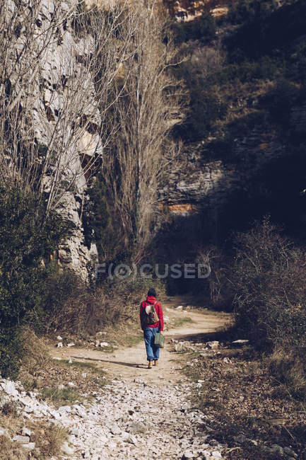 Mulher com mochila e caso caminhando em estrada rochosa em penhascos selvagens majestosos — Fotografia de Stock