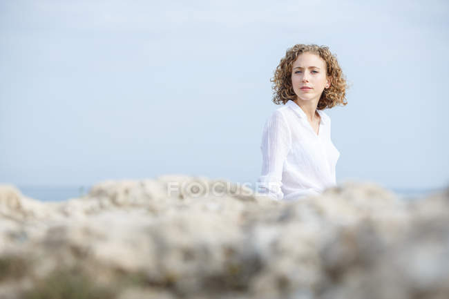 Young thoughtful woman sitting on sea coast and looking at camera — Stock Photo