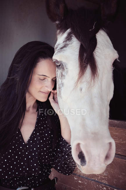 Attractive charming woman with closed eyes touching horse in stall — Stock Photo