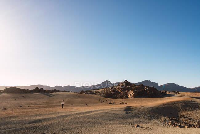 Silhueta de pessoa em terra de areia perto de montanha Teide e vista pitoresca do céu azul em Tenerife, Ilhas Canárias, Espanha — Fotografia de Stock