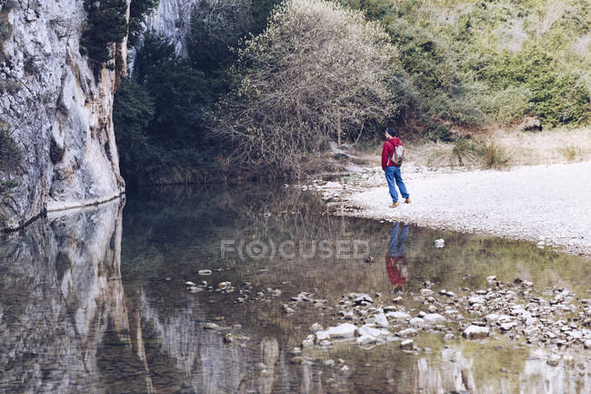 Back view of woman with backpack on coast of mountain river near rock mountain — Stock Photo