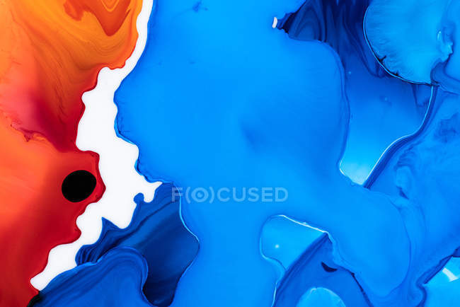 Abstraction of liquid paints in slow blending flow mixing together — Stock Photo