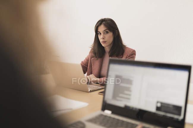 Concentrato giovani donne che navigano su computer portatili e seduti a tavola in ufficio — Foto stock