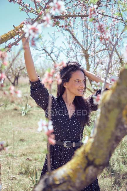 Young smiling woman in dress posing against blooming tree — Stock Photo