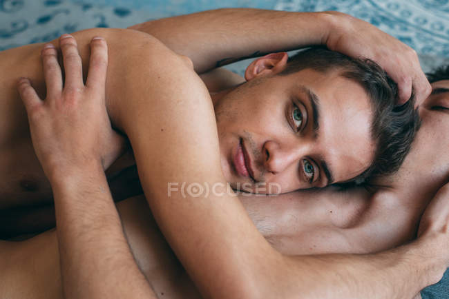 Passionate sexual naked gay couple in an intimate moment lying down in a rug at home — Stock Photo
