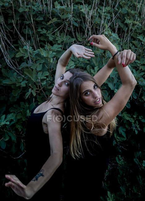 Бічний вид привабливих молодих жінок з закритими очима і витягнутими руками, що стоять біля зеленого куща. — стокове фото