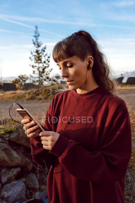 Young hipster woman with piercing and earphones listening music with mobile phone and standing on countryside road — Stock Photo
