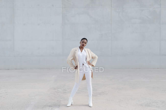 Fashion short haired model in white outfit posing against grey wall — Stock Photo