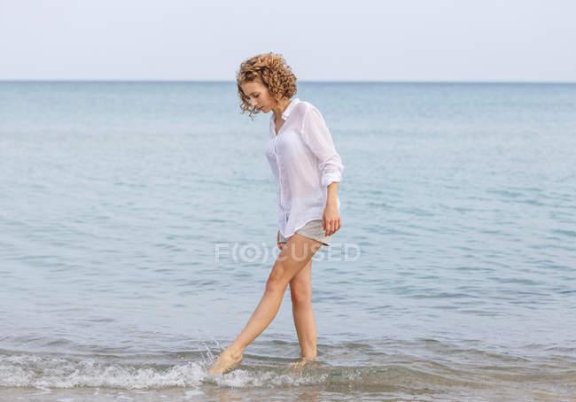 Giovane donna in camicia bianca in piedi in acqua di mare — Foto stock