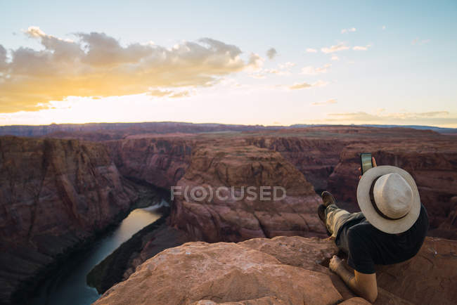 Back view of guy lying down on rock with mobile phone at beautiful canyon and calm river on sunny day on West Coast of USA — Stock Photo