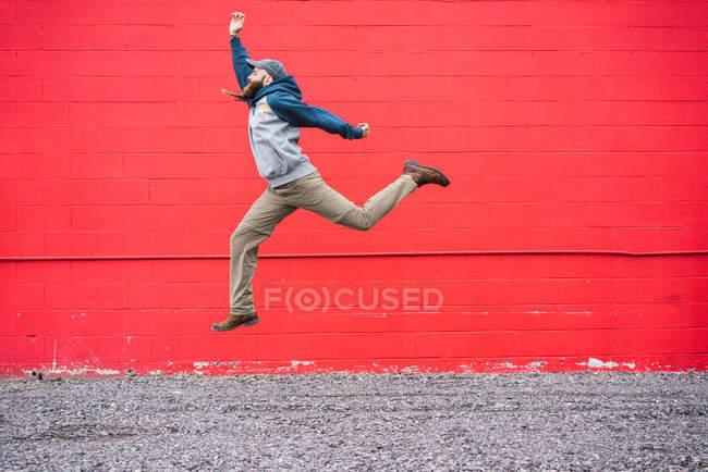 Bello uomo barbuto in abito casual guardando altrove mentre salta verso il muro di mattoni rossi sulla strada della città — Foto stock