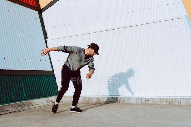Guy in stylish outfit dancing near wall of modern building on city street — Stock Photo