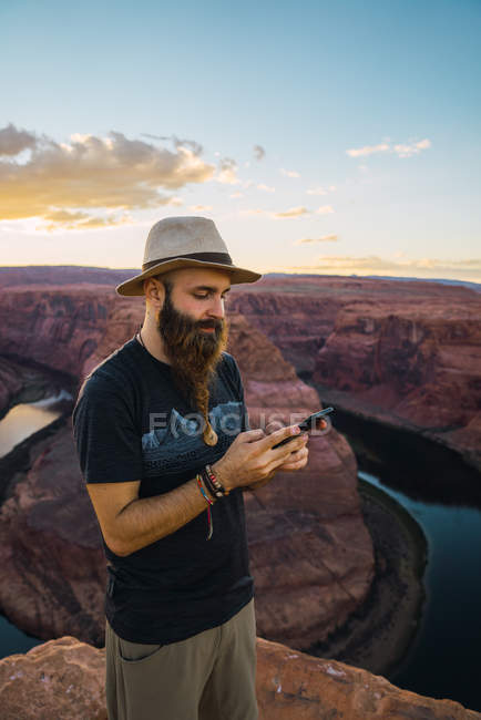 Handsome bearded man in hat on the mobile phone while standing against magnificent canyon and river during sunset on West Coast of USA — Stock Photo